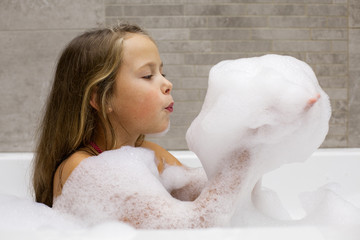 Cute little girl playing with foam in a bathroom