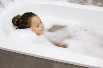Little girl taking a bath with the foam