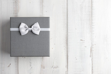 Strict gray gift box with white bow on wooden background