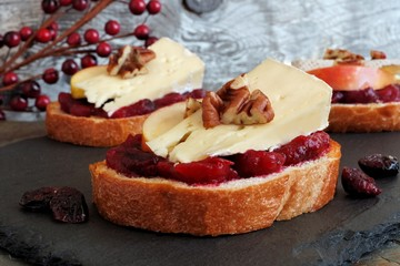 Crostini appetizers with cranberry sauce, apples, brie and pecans on slate server