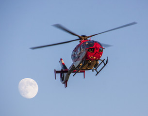 Helicopter with an almost full moon