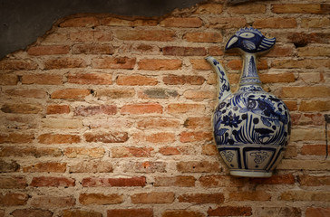 Ceramic bottle on the old wall