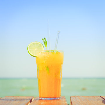Mango mojito on the wooden pier. Concept of luxury tropical vaca