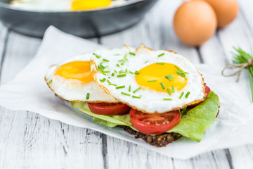 Wooden table with Fried Eggs (on a Sandwich)