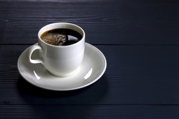 Cup of coffee on the wooden table in blue