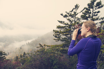 Woman photographing mountains while on a hike