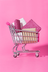 Shopping trolley full of wrapped gifts on pink background