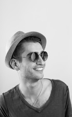 Cheerful young man in hat and sunglasses