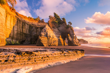 Sunset view of a rocky coast. Tongaporutu beach in Taranaki district, New Zealand, around the famous Three Sisters rock formation