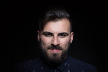 Portrait of handsome man wearing black shirt, black background,
