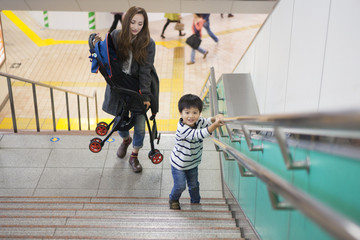 The mother has a stroller and is climbing the stairs of the station