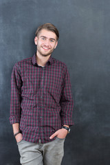 Trendy relaxed young man with a modern haircut standing against