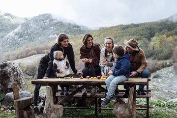 Cheerful friends with kids near the table against mountains in a