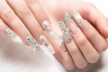 Beautifil wedding manicure for the bride in gentle tones with rhinestone. Nail Design. Close-up.