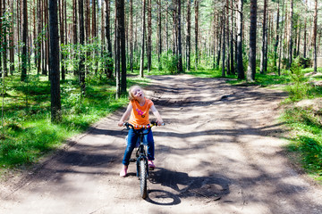 Girl riding her bike in the woods