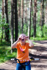 Girl riding her bike in the woods and crying.