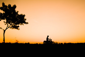 Silhouette of farmer driving motorcycle on field