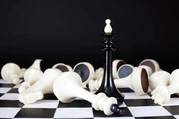 Chess king among defeated enemies. Total victory. Concept with chess pieces against black background
