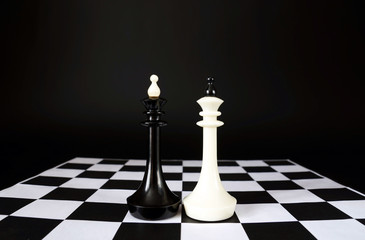 Two chess kings. Battle of equal competitors. Concept with chess pieces against black background