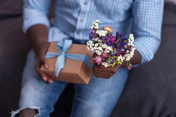 Close up of gift and flowers held by African man