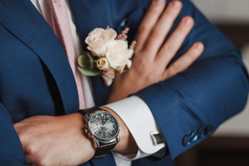 Midsection closeup of confident groom with arms crossed on his chest. Focus on luxury watch at wrist