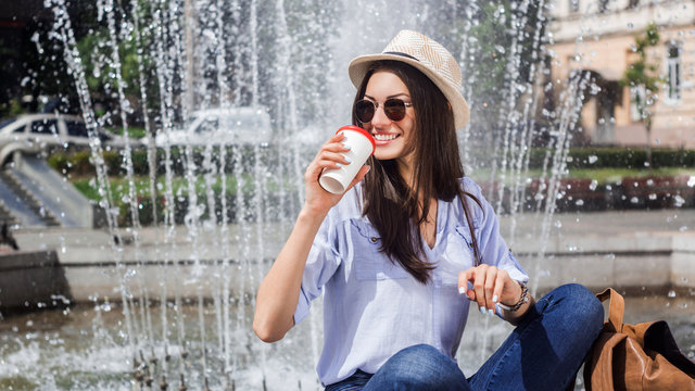 Coffee is always a good idea. A young woman sitting outdoors with a backpack and a takeaway coffee .