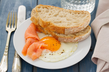 fried egg with smoked salmon and bread on white dish