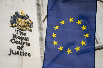 European Union flag flying in front of The Royal Courts of Justice public building in London, UK