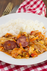meat with sausages, cabbage and rice on white plate on wooden background