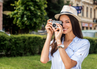 Photography- the beauty of life captured, you make it. Cropped shot of a young woman taking a photo with a vintage camera.