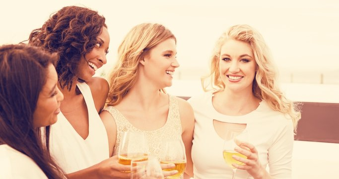 Women drinking wine next to limousine