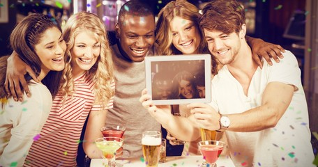 Composite image of happy friends taking selfie with tablet