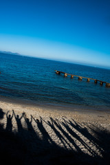 Shadows of people with arms raised on a beach in front of the Mediterranean Sea