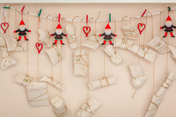 Traditional Christmas holiday wrapped gifts and toys hang on clothespin