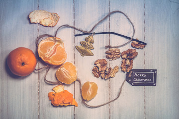 Christmas still life composition with tangerine slices, nuts and Merry Christmas sign on a wooden table