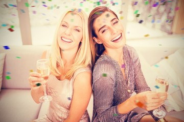 Composite image of portrait of beautiful women holding champagne