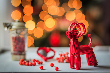 Christmas decoration with red straw goat, some red berries on lighting background