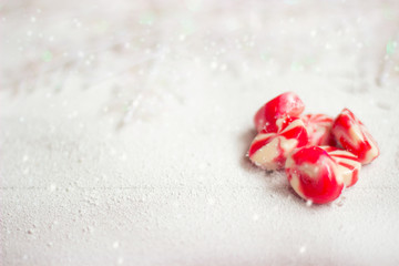 Winter background - candies on white wooden background covered with snow