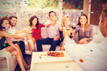Composite image of group of friends toasting cocktail drinks