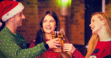 Composite image of cheerful friends having drinks during christm