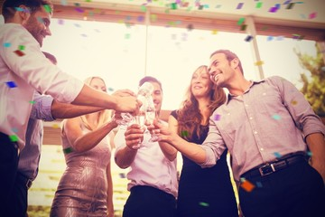 Composite image of low angle view of friends toasting glasses of