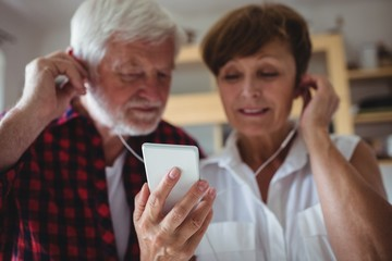 Senior couple listening to music on smartphone