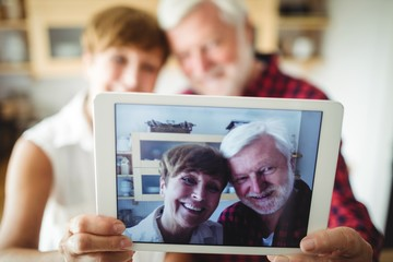 Senior couple clicking a picture on digital tablet