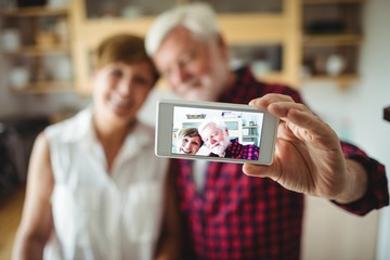 Senior couple clicking a picture on mobile phone