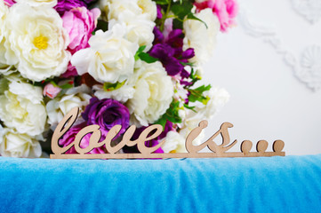 wooden words LOVE IS... against the background of a bouquet flowers