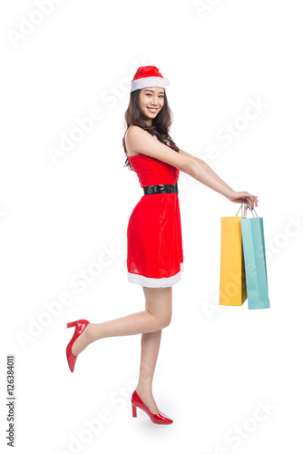 59de33ba82 Full length portrait of a young smiling asian woman holding shopping bags  before christmas