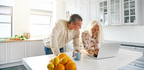 Senior couple relaxing in a kitchen with a laptop Wall mural