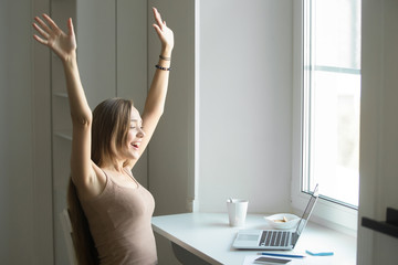 Portrait of a young attractive cheerful woman, celebrating success, victory, sitting at the laptop. Small home office interior. Business concept photo, lifestyle