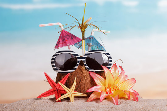 Coconut, sunglasses, starfish and flower in the sand against sea.