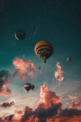Mongolfiere nel cielo con nuvole rosse al tramonto.